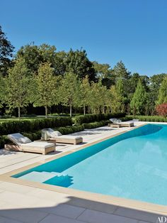 """""""At this Hamptons retreat, the soft blue water of the pool and the surrounding terrace of creamy cast stone creates a centerpiece for a modern but formal courtyard,"""" says Sawyer. """"The linear framework of pleached linden trees, together with boxwood and yew clipped into low hedges, emphasizes the sense of enclosure."""""""