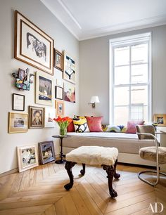 The guest room in the Manhattan apartment of architect Steven Harris and interior designer Lucien Rees Roberts is painted in Benjamin Moore's Classic Gray and features a wall of artworks, including several by Roberts. The stool was made from an Irish Chippendale chair.