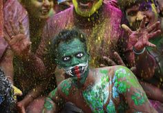 People daubed in colours pose while celebrating Holi in Mumbai Friday. Holi, also known as the Festival of Colours, heralds the beginning of spring and is celebrated all over India.