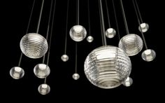 the lighting design by toan nguyen for vibia, is a constellation of globes that seem to float in space like a flock of birds, or a frozen rain shower.