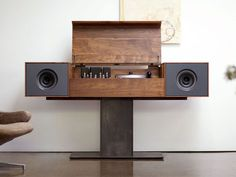 Vinyl made its comeback some time ago, but the player has yet to catch up. Until now. The Symbol Record Console is a bench-made modern record player that pays homage to the all-in-one console hi-fis of the '50s, but bests them with an incredibly clean, modern look. Features include solid American Walnut construction, two  full-range speakers, a second, hidden amplifier and subwoofer, built-in Wi-Fi for streaming music from an iPad or the like, and a hand-built tube amplifier and turntable.