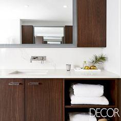 O espelho concede sensação de profundidade e amplitude a este banho que apresenta mármore, tons neutros e madeira escura em sua composição