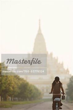 Stock photo of Girl Riding Bicycle in front of Swe Taw Myat Pagoda, Yangon, Myanmar; Premium Rights-Managed, 700-03778324 © Albert Normandin / Masterfile. All rights reserved.