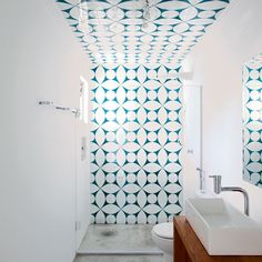 A graphic tile creates a feature wall at the rear of the shower and onto the ceiling.