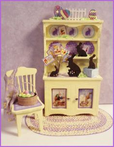 """1/4"""" HIPPITY HOPPITY VIGNETTE  Kit includes: Hutch, chair, rug, easter basket & eggs, apron, chocolate bunnies, accessories, artwork and instructions. Finished Size:  Hutch approx 1"""" w x 1 3/4"""" h. Chair approx 1/2"""" w x 1"""" h"""