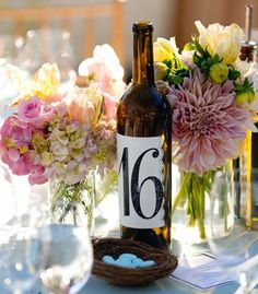 Mason jar centerpieces with table numbers printed on wine bottles.