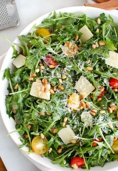 Lemon Arugula Salad with Pine Nuts is a quick and easy salad that is peppery, sweet and satisfying. Arugula is tossed with cherry tomatoes, toasted pine nuts and parmesan cheese and finished off with a lemony,olive oil dressing.// acedarspoon.com #salad #vegetarian