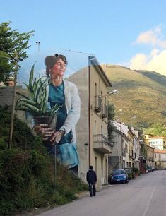 """""""Woman with Aloe Vera Plant"""" – mural by street artist Fintan Magee in Sapri, Italy"""