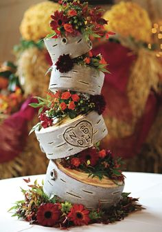 Topsy turvy wedding cake with wooden accents and red flowers. See more from this red fall wedding in the Smoky Mountains at The Lily Barn with casual attire and rustic details! Pics by Madison J Photography | The Pink Bride® www.thepinkbride.com