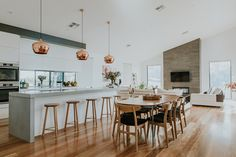 Chifley house in Canberra, Australia designed by Studio Black Interiors. This open plan, kitchen, dining and living area is contemporary but full of warmth and elegance. The concrete kitchen benchtop paired with the warmth of the timber floor, copper pendants and timber stools creates a modern, stylish look.