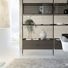 Zenit bookcase with a brown aluminium frame, display cases in transparent grey glass, suspended drawer units in matt caffè lacquered glass.