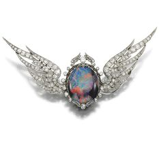 OPAL AND DIAMOND BROOCH, EARLY 20TH CENTURY.  Centring on an oval black opal tablet, within a frame decorated with wing motifs accented with circular-, single- and rose-cut diamonds, set between a pair of engraved en tremblant wings similarly set, brooch fitting and wings detachable, fitted case by Biggs, Maidenhead, Norwood & Farnham, inscribed to the exterior 'WINGS OF THE SUNSET'.