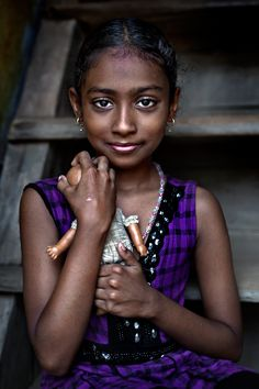 A little girl, she lets herself be photographed outside her home, in the poor area of Fort Kochi, Kerala, India), and holds in her arms her doll, the only toy she has. Kerala, India. (Bruno Tamiozzo/National Geographic Traveler Photo Contest)