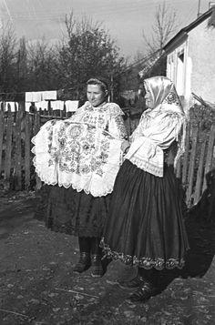 Nesenie na krst. Dievča, ktoré nesie dieťa má čiernu brokátovú sukňu a zásteru so strojovou čipkou. zlatom vyšívané rukávce so stužkou pošitou koálkami. Vlasy zapletené do dvoch vrkočov. D. Lopašov