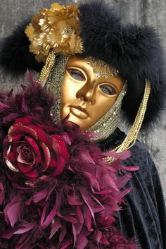 A golden mask with deeply colored costume and ropes of pearls.