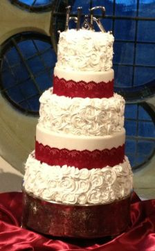 White rosettes with red lace wedding cake