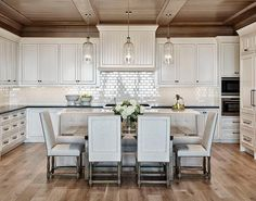 Glass column pendants hang from a stained panel kitchen ceiling over white countertop positioned behind a gray tufted dining bench facing a trestle dining table also seating light gray French dining chairs.
