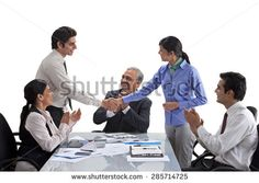 Executives shaking hands with businesspeople applauding - stock photo