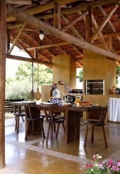 Toda revestida por cimento queimado e com cobertura estruturada em eucalipto roliço, esta cozinha externa mede 110 m² e faz parte de um sítio. Projetado por Vilma Meirelles, o espaço tem arremates de tijolos no piso, que fazem o papel de juntas. O mobiliário robusto conta com mesa colonial e cadeiras da Isto é Brasil.  Fotografia: Evelyn Müller/ Divulgação. Hut House, Dirty Kitchen, Jungle House, Tropical Houses, Rustic Style, Home Interior Design, My Dream Home, Beach House, Pergola