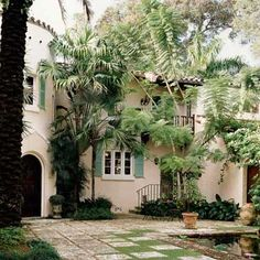 This south Florida entry courtyard, dotted with palms and other tropical plants, welcomes guests in style. Homeowner and decorator                                         Jenny Peters worked with architect Rafael Portuondo to renovate the early 20th-century home