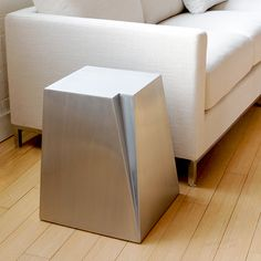 GLACIER END TABLE  Inspired by the rugged, Canadian landscape, this sculptural accent table is crafted from brushed stainless steel creating a solid form that subtly reflects its surroundings. This sculptural accent table looks great in multiples.