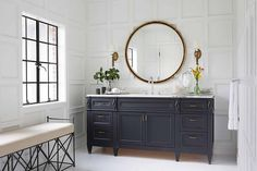 Stunning bathroom features walls cla din square decorative moldings lined with a round black and gold mirror over a navy blue footed washstand adorned with brass pulls.