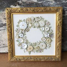 Handsewn framed picture of a wreath using white buttons with embroidered leaves and stems. It takes me over 100 hours to hand sew all the