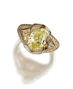 FANCY INTENSE YELLOW DIAMOND AND DIAMOND RING, BULGARI Set at the centre with an oval fancy intense yellow diamond weighing 3.01 carats, within baguette, calibré- and brilliant-cut diamond surrounds, mounted in yellow gold, signed Bulgari and numbered, maker's marks.