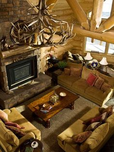 Comfortable sofas form a conversation group around the fireplace. The Huntsmans chose soft green colors compatible with the dominant wood tones and the view outside the enormous window. An antler chandelier provides an appropriate centerpiece.