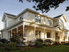Traditional farmhouse features, oversized light fixtures and period-appropriate plantings make the front yard and porch pop.