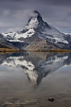 Mount Matterhorn, in the grey sky of the morning, reflecting in the Stelisee lake.