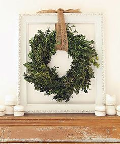 Simple holiday decor greenery wreath hanging in an empty frame | Design Ideas Using Empty Frames
