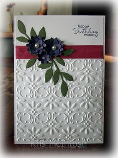 "Emboss  Whisper White card stock w Finial Press Embossing Folder, Rose Red 1/2″ Seam Binding, Stamp ""happy birthday wishes"" Petite Pairs stamp set  Elegant Eggplant ink,leaves Always Artichoke card stock use the Little Leaves Sizzlit and attach them over the ribbon on the left hand side. Punch two sets of flowers from Elegant Eggplant card stock using the Boho Blossom punch. Attach the flowers to each other and to the card front using Mini Glue Dots add some Basic Pearls."