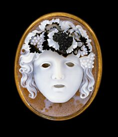 Gold frame enclosing sardonyx cameo mask of a Bacchante, facing front, mouth open as if screaming, head crowned with vine leaves and bunches of ripe grapes. Signed MORELLI (Nicolo Morelli, 1771-1838). Formerly Esmerian Collection.