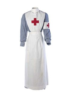 """Red Cross Uniform: 1914-1918, English, cotton chambray, starched cotton apron, red woolen cross on big, white cotton armband and white cotton cap. """"First World War volunteer nurse's uniform. Worn by Kathleen Falls who initially worked as a nurse at Torbay Hospital and subsequently studied for a qualification in pharmacy, receiving her certificate in 1917."""""""