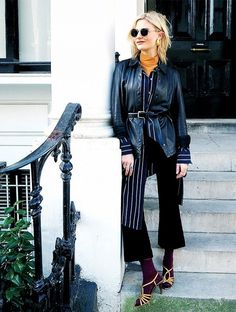 Pandora Skyes wears a belted leather jacket over a long striped button down with black flare pants, socks, and gold strappy heels