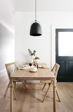 Simple Nordic Design. Dining room interior with black pendant light and beautiful wooden table and chair set.