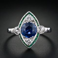 Gorgeous art deco! / deep blue round sapphire weighing 1.40 carats within a navette shaped silhouette. The sapphire is bordered by one delicate row of emeralds and accented by .30 carats of transitional round brilliant and old European cut diamonds. The ring is constructed in 14 karat white gold.