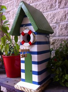 A beach themed birdhouse modeled after beachside changing rooms. It took a while getting a seamless look for the main body but it makes the striping stand out more.