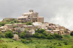 Ujué (Navarra) Un racimo de casas alrededor de la iglesia-fortaleza de Santa María (levantada entre los siglos XI al XIV). Ujué es un enclave defensivo de calles empedradas que conserva su aspecto medieval. Una atalaya desde la que, en días despejados, pueden verse los Pirineos al norte y la ribera del Ebro y la silueta del Moncayo por el sur. La imagen de la Virgen de Ujué está considerada una obra cumbre del románico navarro.