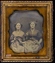 Two women holding shuttles, thread in mouth, wearing necklace, daguerreotype ? brooch. Mill workers. Gold; brooch.