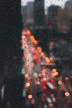 Rain on windows for a blurry background of traffic lights