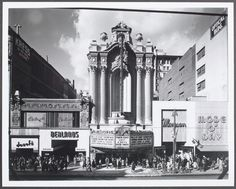 In Downtown Los Angeles, frontal view of the Los Angeles theatre showing Doself's and Berland's stores at left and Mode O' Day and Mayson stores at right    USC Digital Library