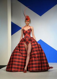 """""""Dressed to Kilt""""; Young New York City model modelling a swimsuit-typed bodice with an open half-hoop-style skirt long to the floor that is cardinal red & black tartan pattern in design."""