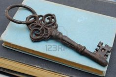 old antique key on blue  books Stock Photo
