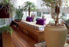 Poucas e impactantes plantas e vasos, deck de madeira (ou imitando), pedriscos, um futon algumas almofadas