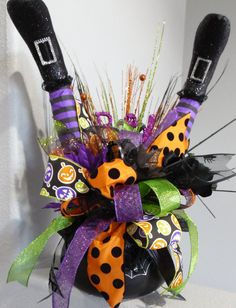 Celebrate the upcoming Halloween season with this cute centerpiece that features all the colors of Halloween. This one of a kind ceramic witches cauldron is filled with glittered leaves and stems, black roses, glittered spiders, a large wired bow with 7 different complimentary Halloween inspired ribbons and so much more!!! The focal point of this centerpiece are the witches feet and it looks like she is cooking in her own broth!!! This centerpiece measures 22 inches tall, by 22 inches wide…