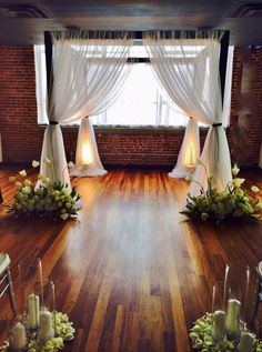So exciting !! A Dramatic but simple ceremony site, a drapped huppa grounded by an arrangement of white french tulips and a triple candle arrangement in mounds of petals. Perfect Bride & Groom, Perfect Design For Them ! #stemsevents #stemsstl #jennythomassonaifd #weekend — with Stems Florist www.stems4weddings.com — at Lumen Private Event Space by Jenny Thomasson AIFD CFD.
