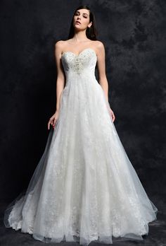 Eden Bridals  Lace gown with tulle overlay lined with Peau de Soie. Strapless sweetheart bodice has been encrusted with crystalized beading accents, and A-line gown with chapel length train.