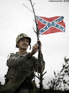 A U.S. Marine with a confederate flag, Okinawa Japan, 1945.